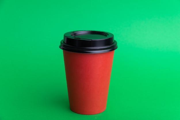 Foto de una taza para llevar roja con gorra negra sobre verde
