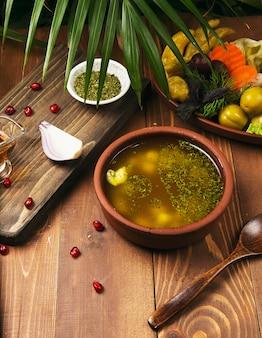 Una foto de un tazón de sopa de pollo tradicional servido en un tazón de olla