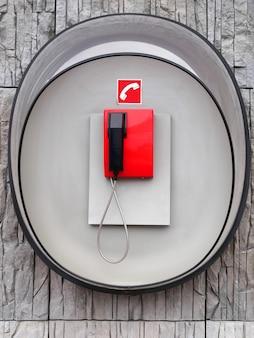 Foto de teléfono rojo en la pared gris del edificio moderno