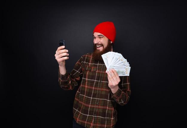 Foto del tipo sonriente afortunado que celebra la victoria después de hacer apuestas utilizando la aplicación móvil de juegos de azar en su teléfono.