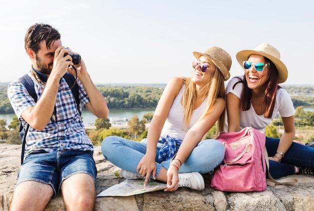Foto de toma de hombre de dos mujeres de moda felices en cámara