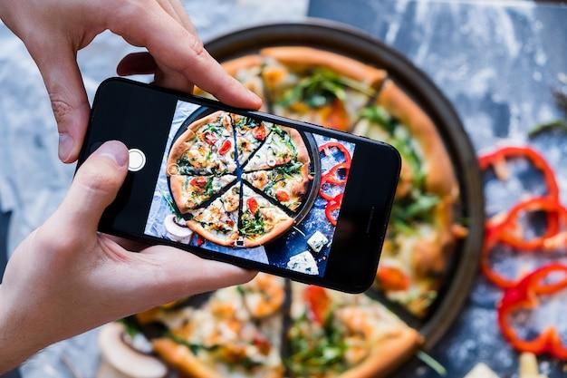 Foto de toma de pizza de hombre con smartphone vista de primer plano del proceso