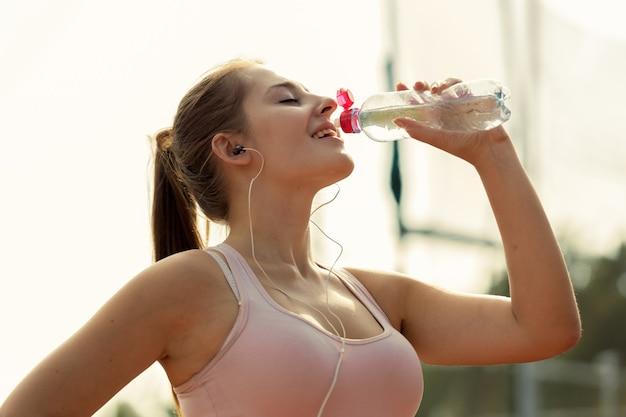 Foto de tonos de hermosa mujer bebiendo agua después de correr en un día caluroso