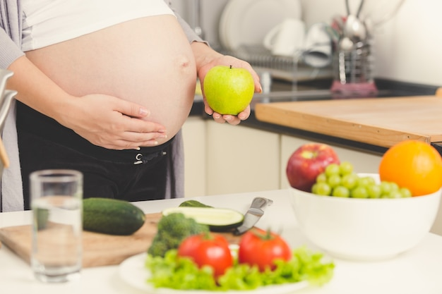 Foto de tonos de mujer embarazada posando con manzana verde mientras cocina