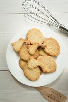 Foto en tonos de primer plano desde arriba del plato con galletas y utensilios de cocina en el escritorio blanco