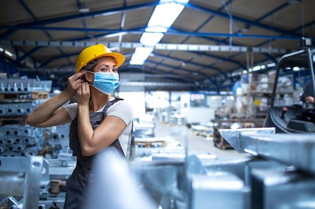Foto de trabajadora de fábrica en uniforme y casco poniéndose mascarilla en planta de producción industrial