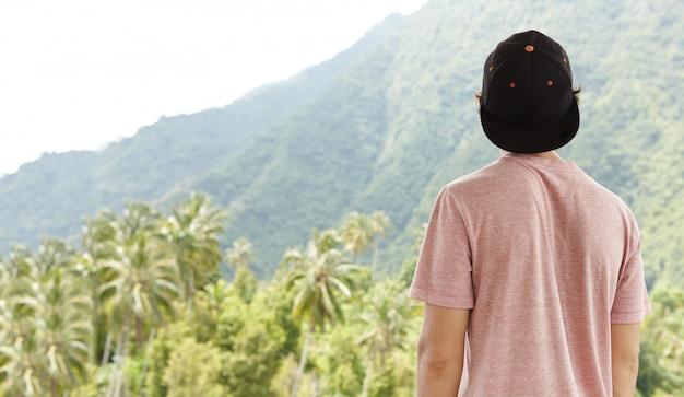 Foto trasera del joven viajero caucásico vistiendo snapback sintiéndose libre y en paz durante su viaje en vacaciones de verano