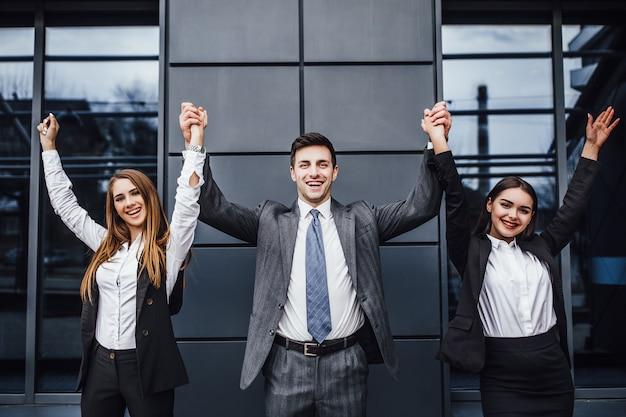 Foto de tres jóvenes empresarios felices en ropa formal celebrando, gesticulando, manteniendo los brazos levantados y expresando positividad.