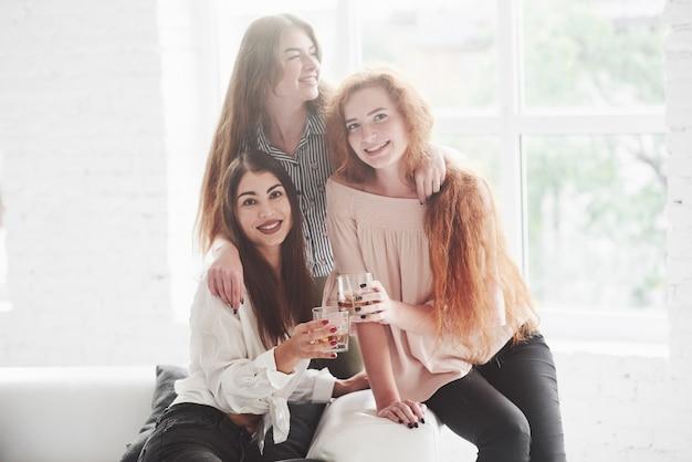 Foto de tres niñas de interior sosteniendo vasos de whisky y sonriendo