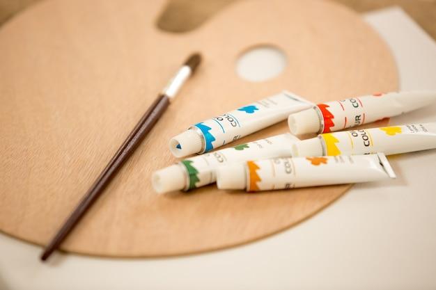 Foto de tubos de pintura de aceite un pincel acostado sobre paleta de colores