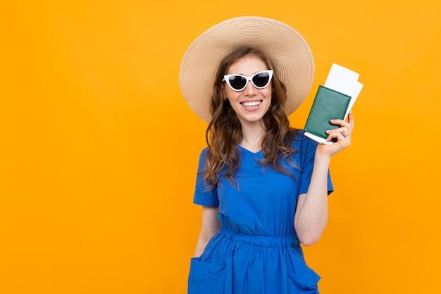 Foto de un turista con pasajes de vacaciones y pasaporte sobre un fondo naranja