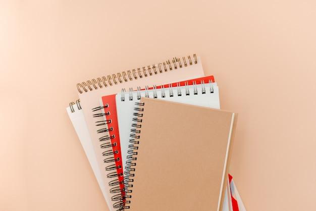 Foto de vasos y libretas sobre un fondo abstracto beige