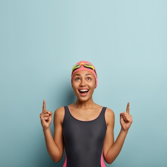Foto vertical de alegre mujer de piel oscura disfruta de su pasatiempo favorito y descanso activo de verano, vestida con traje de baño