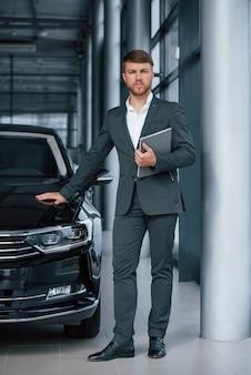 Foto vertical. empresario barbudo con estilo moderno en el salón del automóvil