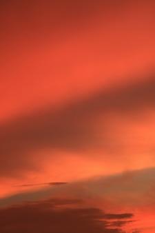 Foto vertical de la gradación de color naranja y la capa de nubes del cielo del amanecer en tailandia