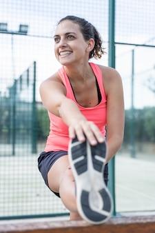 Foto vertical de una mujer en ropa deportiva estirando su pierna en un tenis al aire libre