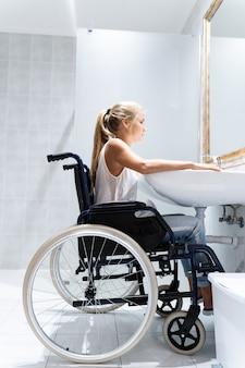 Foto vertical de una mujer rubia sentada en una silla de ruedas en un baño