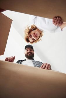 Foto vertical. pareja feliz juntos en su nueva casa. concepción de mudanza