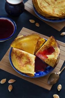 Foto vertical de tortitas finas de calabaza con mermelada de bayas en placa azul