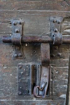 Foto vertical de una vieja cerradura de una puerta oxidada y con la madera vieja. villefranche de conflent en francia