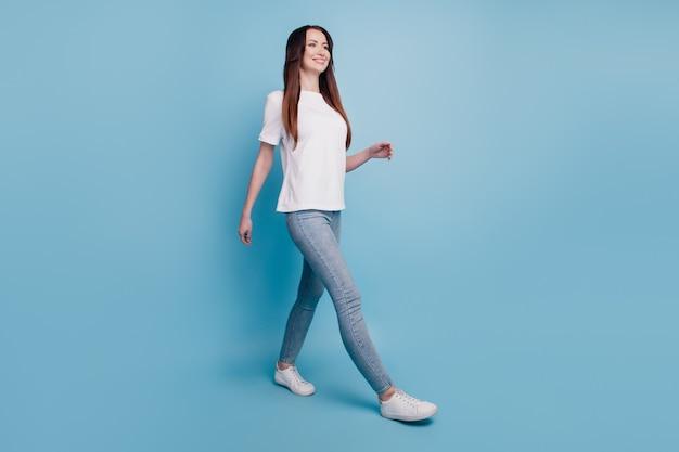 Foto vista de cuerpo entero de mujer caminando aislado sobre fondo azul.