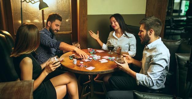 Foto de la vista lateral de los amigos masculinos y femeninos que se sientan en la mesa de madera.