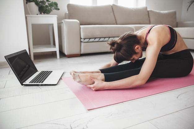 Foto de vista lateral de una dama caucásica haciendo yoga en el suelo y usando una computadora portátil mientras se estira