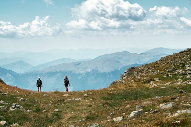 Foto de vista posterior de excursionistas de pie al borde de una colina en la riviera francesa