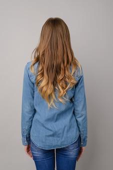 Foto de vista posterior de la mujer en ropa de jeans con fondo gris aislado de pelo rizado