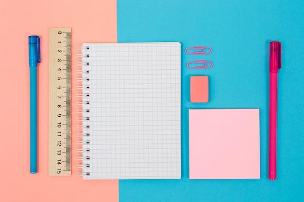 Foto de vista superior de bolígrafos regla clips de cuaderno pegatinas de borrador sobre fondo azul y rosa bicolor