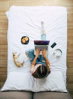 Foto de vista superior de cuerpo entero de una joven morena en ropa casual mientras trabaja con una computadora portátil en la cama. niña feliz estudiando con un perro en casa