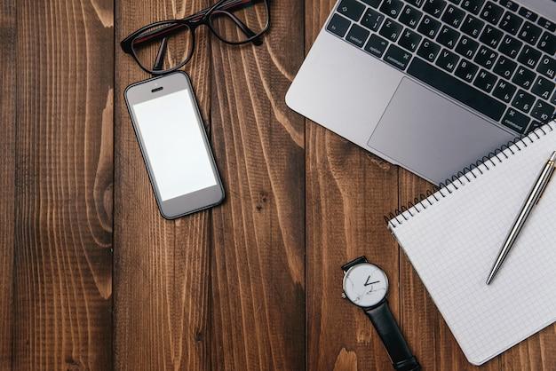 Foto de la vista superior del escritorio de oficina de madera con fondo de computadora portátil, anteojos, reloj, teléfono y cuaderno