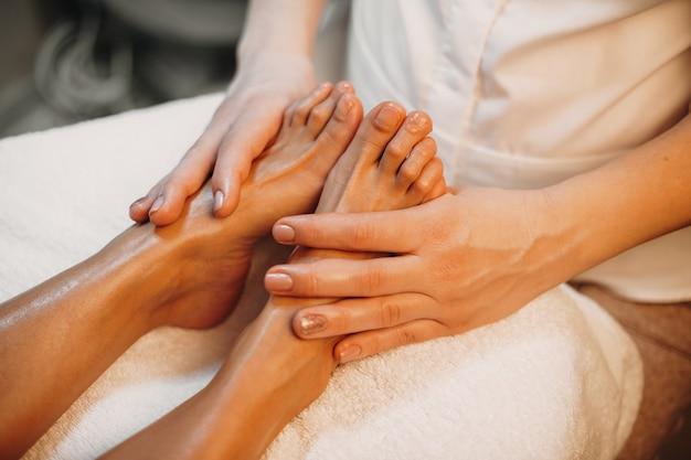 Foto de la vista superior de un masajista caucásico con una sesión de masaje de pies en el salón de spa