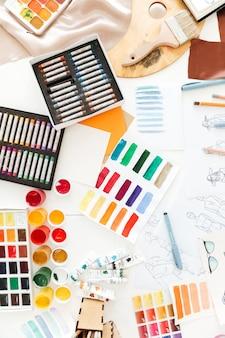 Foto de la vista superior de muchas ilustraciones de moda y crayones sobre la mesa