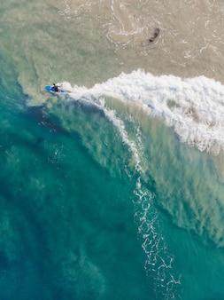 Foto de vista superior de una persona con una tabla de surf nadando en la playa de varkala