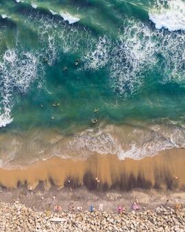 Foto de vista superior de personas nadando y sentadas en la playa de varkala