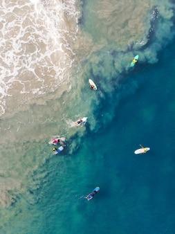 Foto de vista superior de personas con tablas de surf nadando en la playa de varkala