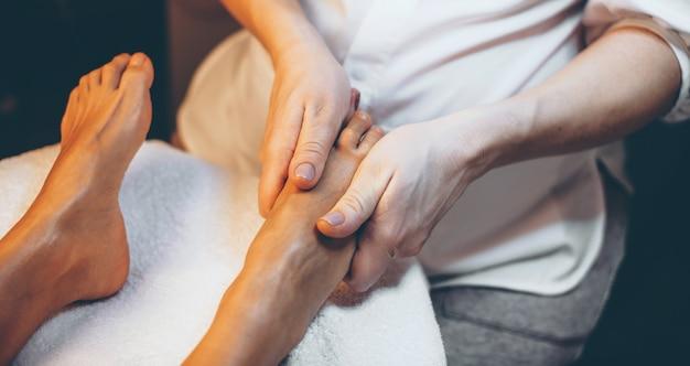 Foto de la vista superior de una sesión de masaje de pies en el salón de spa hecho a una mujer