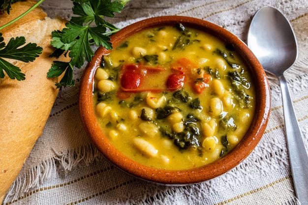 Foto de vista superior de sopa de verduras en el cuenco de barro con pan y verduras sobre la mesa