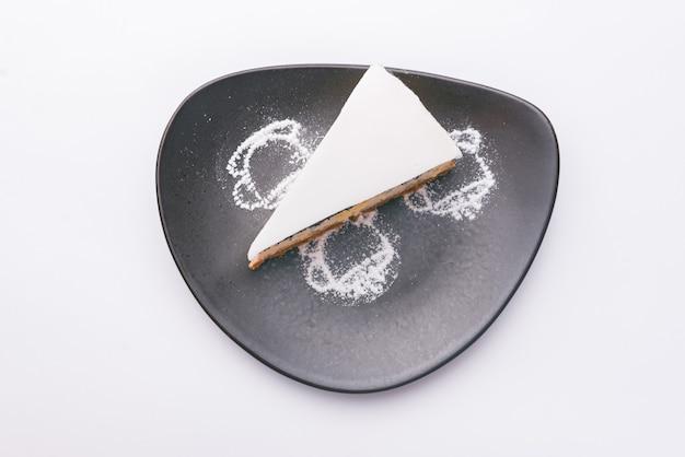 Foto de la vista superior de la tarta de amapola blanca en un plato oscuro