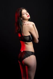 Foto de vista vertical hermosa dama tímida en bragas de sujetador de boudoir de bikini de encaje. tierna delgada forma delgada pared negra aislada