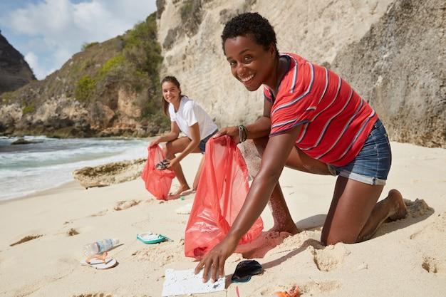Foto de voluntarios activos responsables que recogen basura en una playa de arena
