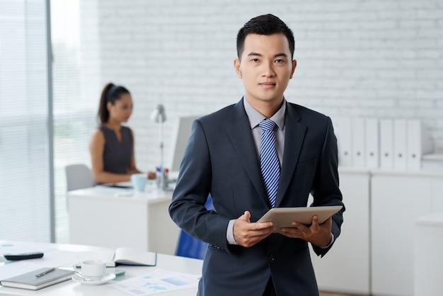 Foto de waistup del hombre de negocios asiático de pie en el moddle de la oficina y sosteniendo una tableta digital