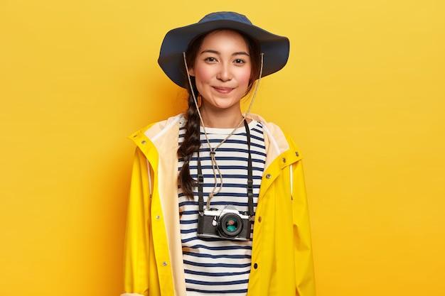 Fotógrafa talentosa hace tomas profesionales durante un viaje de aventura, usa cámara retro, usa sombrero elegante, impermeable amarillo, disfruta de las vacaciones
