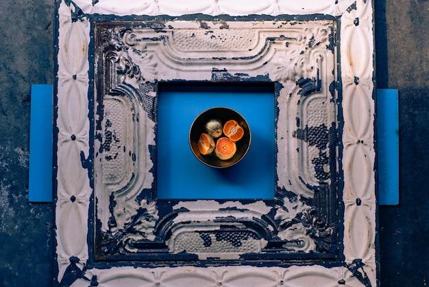 Fotografía abstracta de mandarinas chapadas en metal en un recipiente sobre una superficie azul y madera
