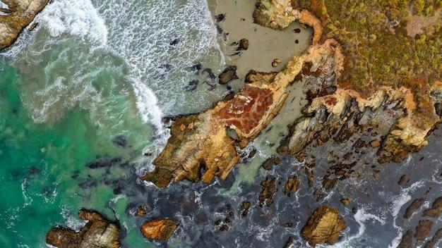 Fotografía aérea de arrecifes de coral en la costa del mar con increíbles texturas de agua y olas.