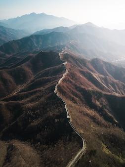 Fotografía aérea de drones de la gran muralla de china con la luz del sol brillando a un lado