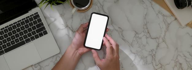 Fotografía aérea de un empresario masculino que usa un teléfono inteligente con pantalla en blanco para encontrar información para su trabajo