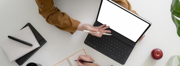 Fotografía aérea de empresarios que trabajan junto con una tableta de pantalla en blanco y otros suministros