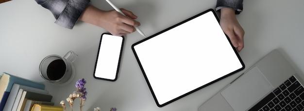 Fotografía aérea de estudiante universitaria haciendo asignación con tableta de pantalla en blanco y teléfono inteligente